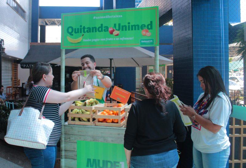 Pessoas em volta da Quitanda Unimed com frutas