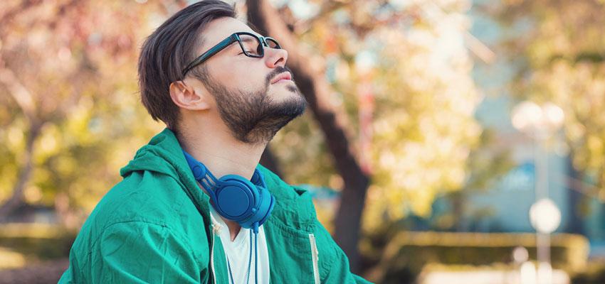 Homem de olhos fechados respirando ao ar livre sem sintomas de rinite