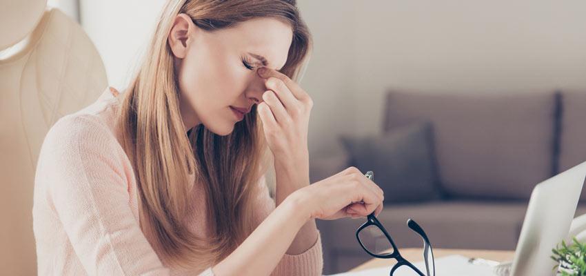 Mulher com mão no nariz tentando aliviar dor da sinusite