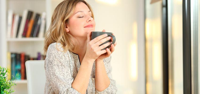 Mulher sorrindo cheirando uma xícara