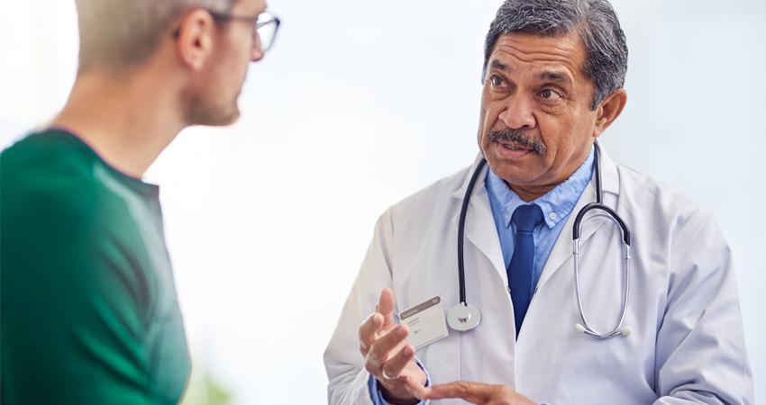 Médico orientando paciente sobre os perigos do HPV no homem