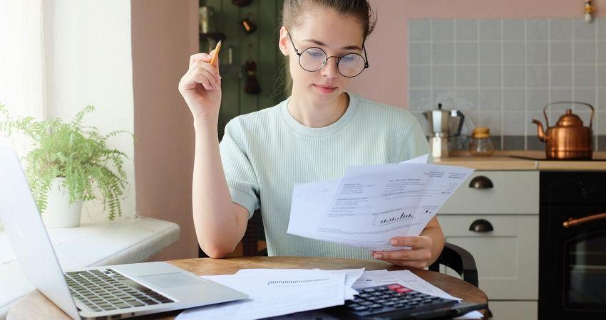 Jovem mulher verificando contas a pagar