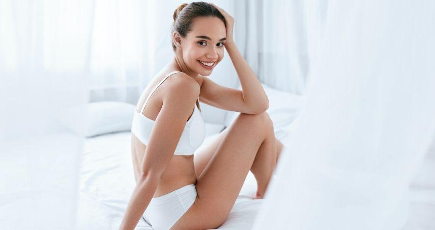 Mulher sentada na cama sentindo-se empoderada após praticar o pompoarismo