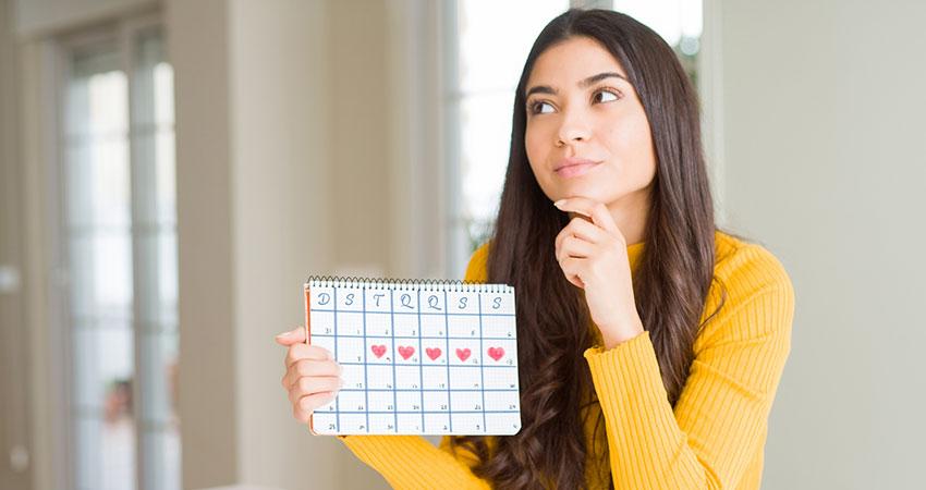 Mulher pensativa segurando calendário do seu período fértil