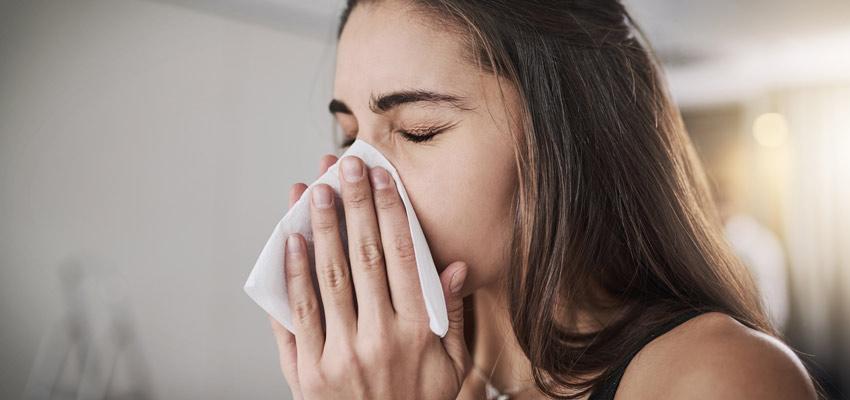 Mulher assoando nariz depois de contrair uma das arboviroses