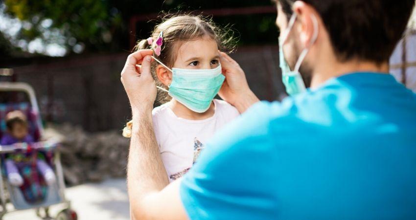 Pai colocando máscara de proteção na filha para evitar a contaminação pelo coronavírus