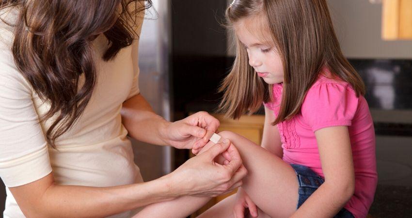 Mãe fazendo curativo na filha após acidente doméstico