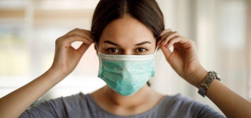 Mulher colocando máscara de proteção contra a covid-19