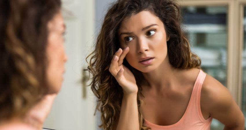 Mulher analisando terçol no olho
