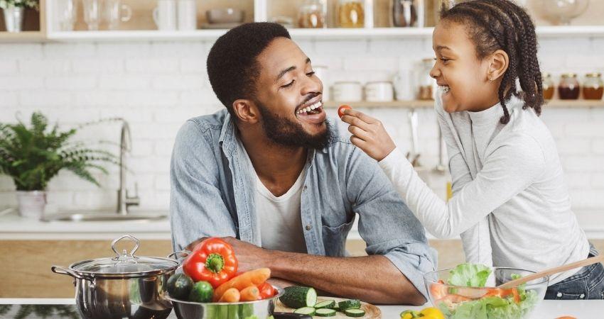 Pai e filha fazendo refeição na cozinha