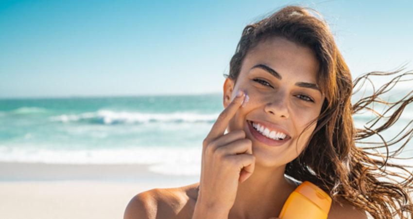 Mulher prevenindo cancer de pele passando protetor solar