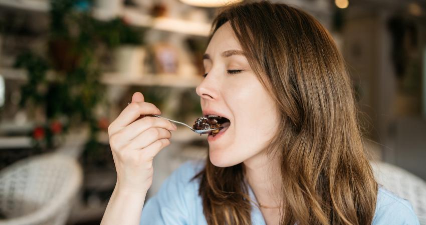 Mulher comendo bolo de chocolate para diabeticos