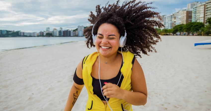 Mulher correndo feliz na praia